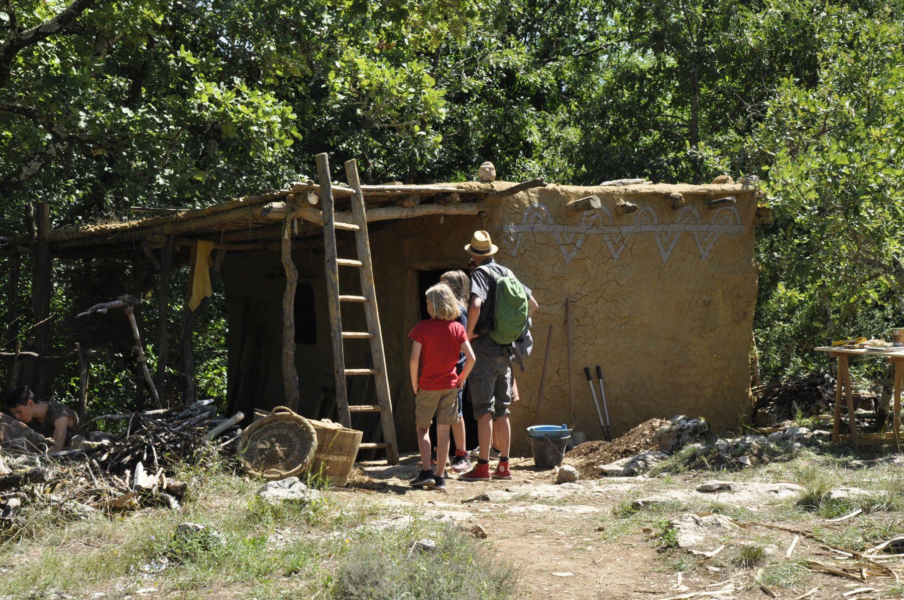 Randa Ardesca Archéosite d'Ardèche - Visiteurs devant une maison gauloise